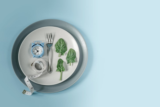 Синие часы, вилка, листья шпината и рулетка на серой тарелке, диета и концепция прерывистого голодания