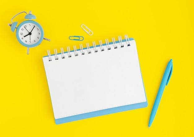 青い時計、空白のノートブック、黄色の背景の上にペン。締め切りコンセプト、モックアップ