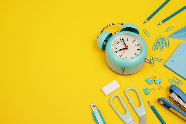 Blue clock with various devices placed on a yellow background.