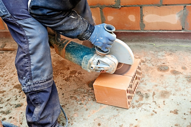 Blue clollar worker cutting concrete block with electric saw