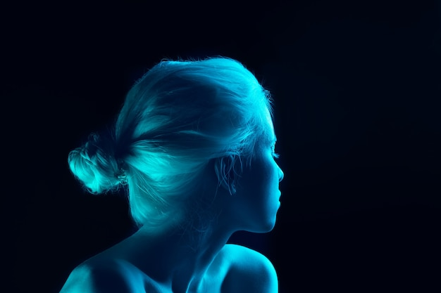 Blue. close up portrait of beautiful albino girl on dark background in neon light. blonde female model with dreamlike make-up and well-kept skin. concept of beauty, cosmetics, style, fashion.