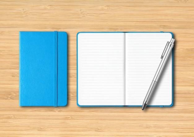 ペンで裏打ちされた青い閉じたノートと開いたノート。木製の背景に分離されたモックアップ