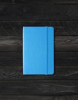 Макет синий закрытый блокнот, изолированные на фоне черного дерева