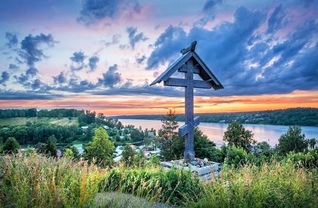 Голубые облака в закатном небе над волгой с горы левитан в плесе летним вечером и деревянный крест погоста возле храма. надпись: поклонение кресту