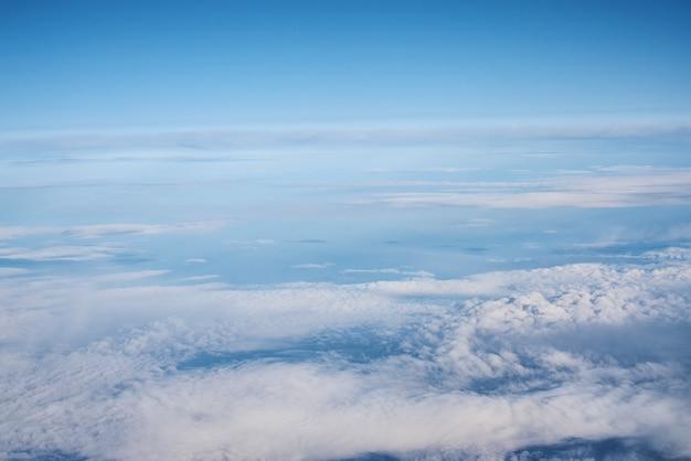 青い曇り空、飛行機の窓からの眺め。 cloudscapeの空撮