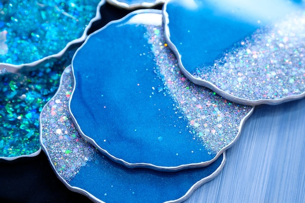 The blue coasters is made of epoxy resin. stand, tray, or decorative element on wooden shelf.