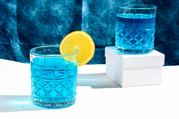 ブルーカクテルドリンクオレンジ色のブルードリンクとグラス2杯
