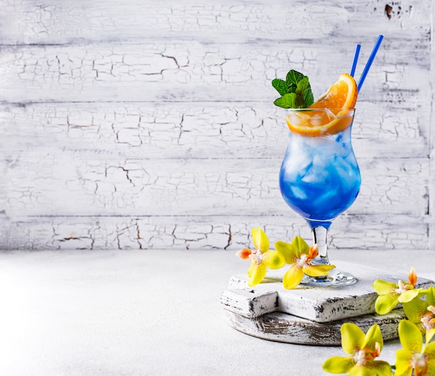 Blue cocktail drink with ice and orange