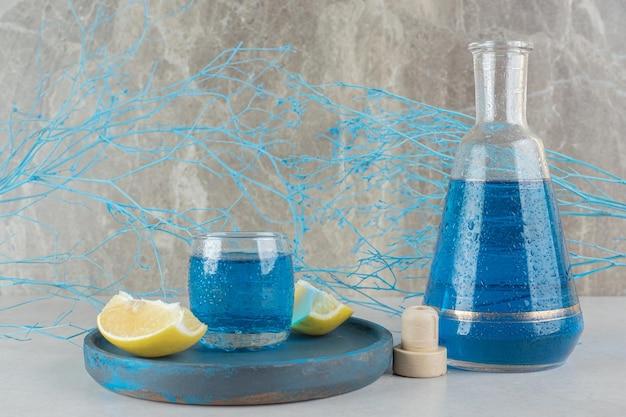 Cocktail blu in vetro e bottiglia con fette di limone sulla zolla blu