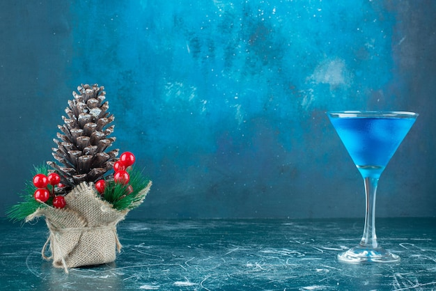 Blue cocktail in a glass next to christmas ornament on marble.