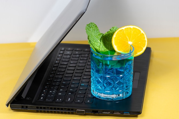 ラトップキーボードの青いカクテルグラス