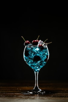 Blue cocktail in a glass with ice and cherry