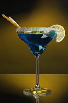 色の背景にガラスの青いカクテル