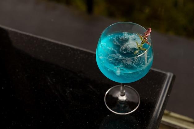 黒いテーブルの上に青いカクテル