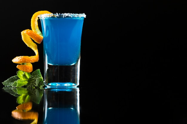 Blue cocktail in shot glass with orange peel and mint