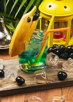 Blue cocktail with banana dolphin decoration, black grapes on a wooden board