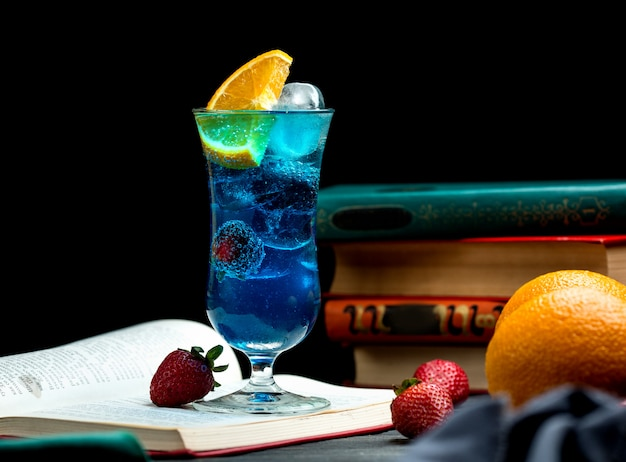 Blue cocktail with blackberry, orange slice, strawberry and ice