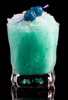 Blue cocktail with cherry isolated on black