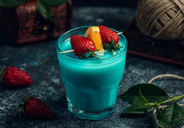 Blue cocktail with fresh strawberries and orange
