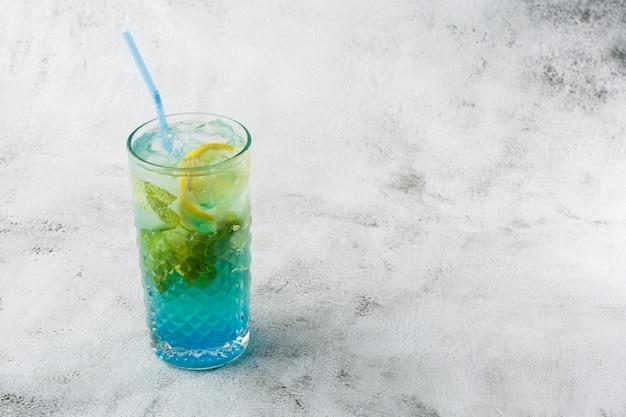 アイスキューブとレモンとライムのスライスと青いカクテル。ブルーラグーンの夏のカクテル。アイスブルーレモネード。俯瞰、コピースペース。カフェの広告。バーメニュー。横の写真。