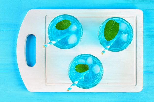 Blue cocktail with ice and mint in glasses on a white wooden board on a blue table, top view