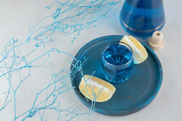 Blue cocktail with lemon slices on blue plate.