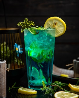 Blue cocktail with mint and lemon in a glass.