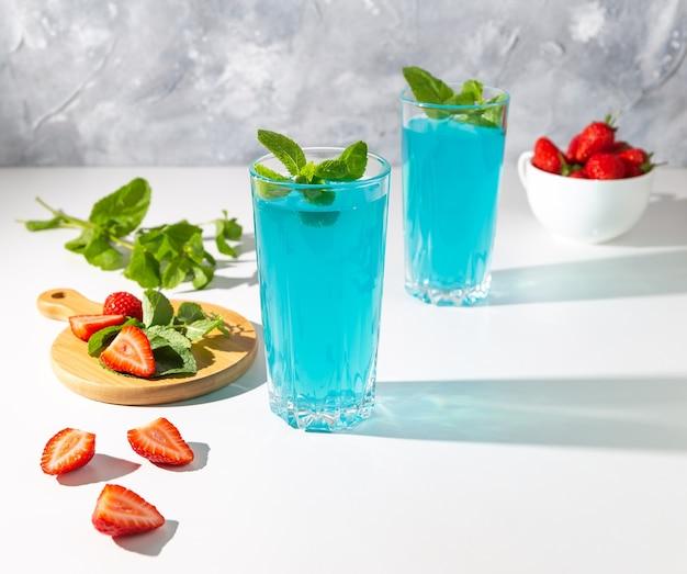 イチゴと白いテーブルの上にミントと青いカクテル