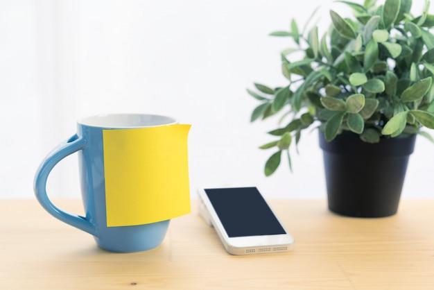 Голубая кофейная чашка и post-it note на деревянной столешнице