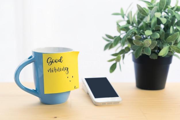 Кофейная чашка синего цвета и записка с надписью «доброе утро» на деревянном столе