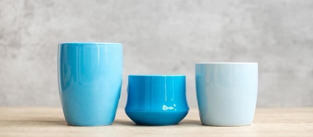Голубая кофейная чашка и кружка чая на предпосылке деревянного стола утром, пустое пространство экземпляра для текста. международный день кофе и концепция распорядка дня