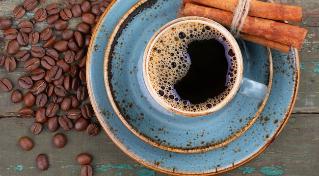 Blue coffee cup and coffee beans with cinnamon sticks on an old wooden background