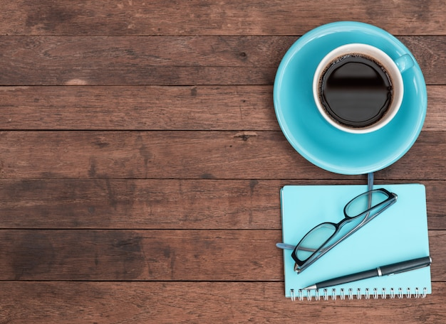 Blue coffee cup, eye glasses, pen and notebook on grunge wooden table, top view with copy space