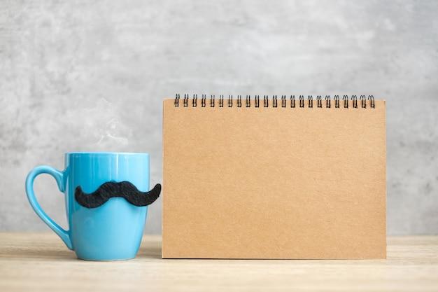 Синяя кофейная чашка или кружка с черными усами и пустой бумажный блокнот или календарь на столе. пустая копия пространства для текста. голубой ноябрь, счастливый день отца и концепция международного мужского дня