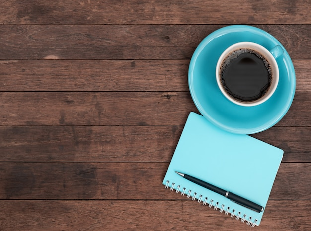 Blue coffee cup, pen and notebook on grunge wooden table, top view with copy space