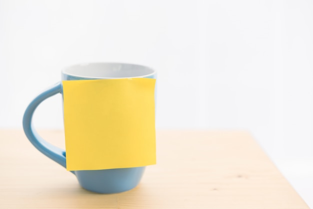 Blue coffee cup and post-it note on wooden table top