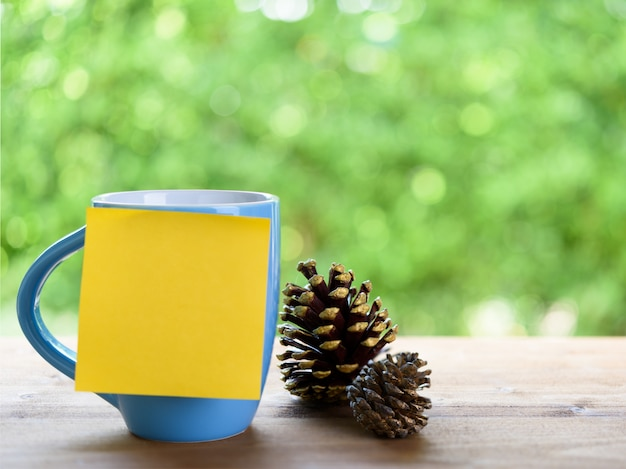 Blue coffee cup, post it for text and pine cones on wood table
