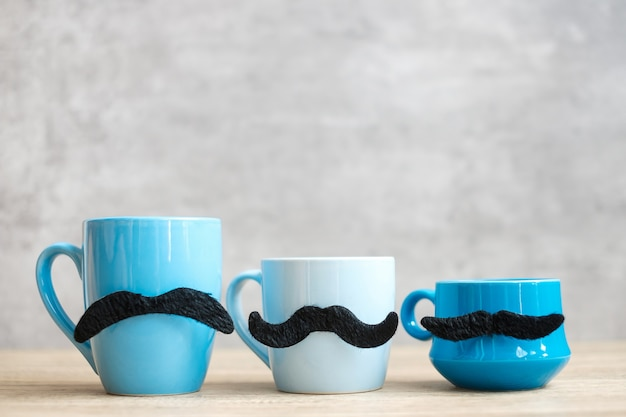 Blue coffee cup and tea mug with black mustache decor on wood table background in the morning. blue november, happy father day and international men day concept