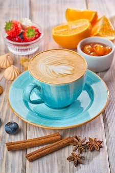 Blue coffee cup with cappuccino, cinnamon and anise. breakfast concept