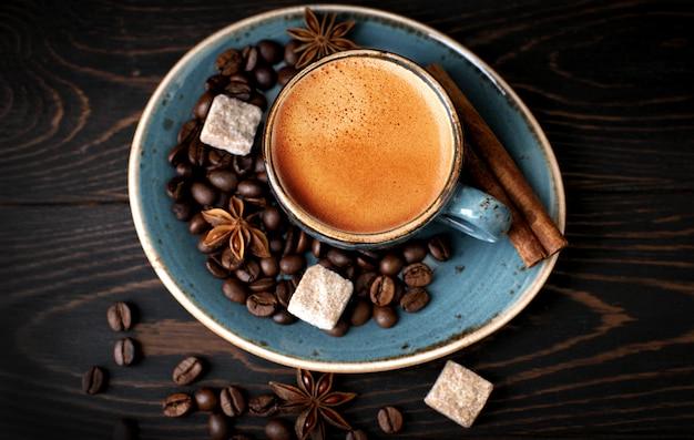 Blue coffee cup with coffee beans and cinnamon on a wooden table