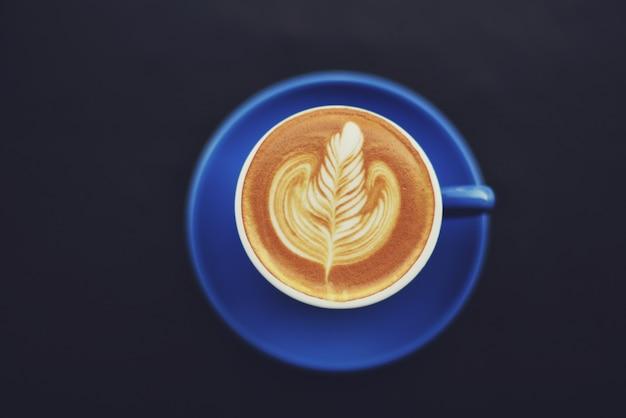 Tazza di caffè blu con un orecchio disegnato nella schiuma