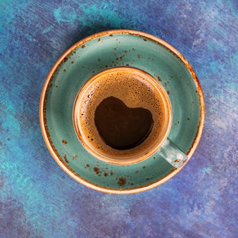Blue coffee cup with heart shape made of foam on blue wooden background.