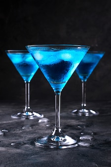 Синий холодный коктейль в бокале мартини со льдом и прозрачными каплями росы