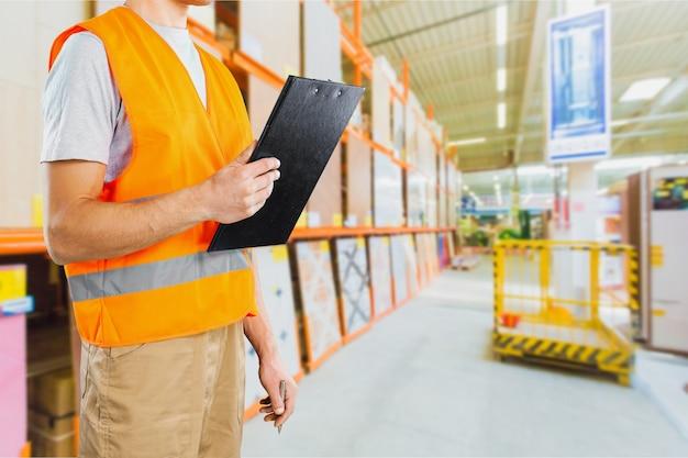 ブルーカラー労働者。倉庫にクリップボードを持っている男