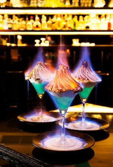 Blue color cocktail topping by whipping cream on fire