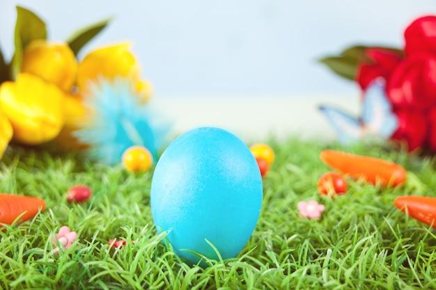 Пасхальные яйца синего цвета в траве с цветами тюльпанов на заднем плане.
