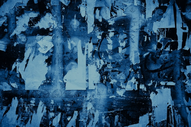 Blue color grunge background. scraps of old paper posters on the wall