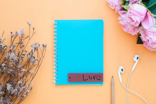 Blue color notebook on orange background, memo, diary and calendar