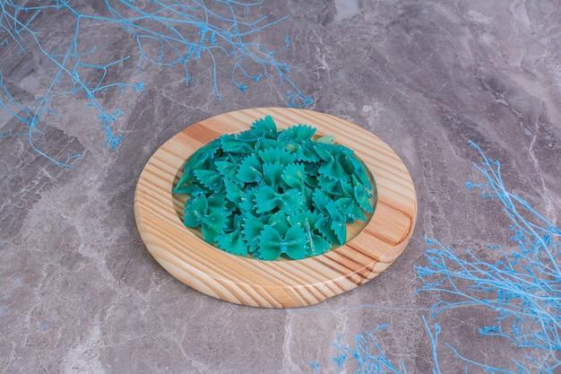 木製の大皿に青い色のパスタ。