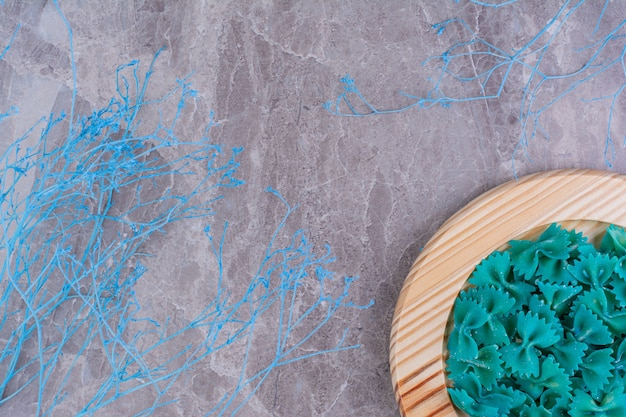 Blue color pastas in a wooden platter.